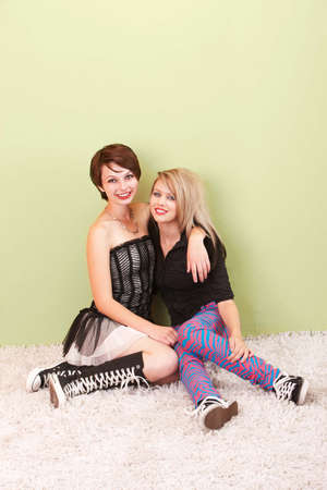 bff: Two beautiful teen punk girls sit friendly with each other in front of a green background. Stock Photo