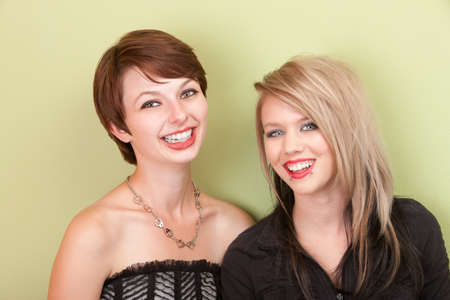 Two young punky looking teens smile in front of a green wall. photo