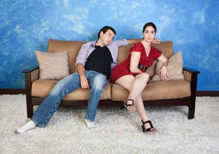 annoying: Zirytowany młoda kobieta siedzi na kanapie z leniwym chłopakiem