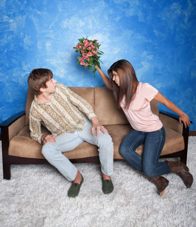 breakup: Angry girl gestures to hit boyfriend with flower bouquet