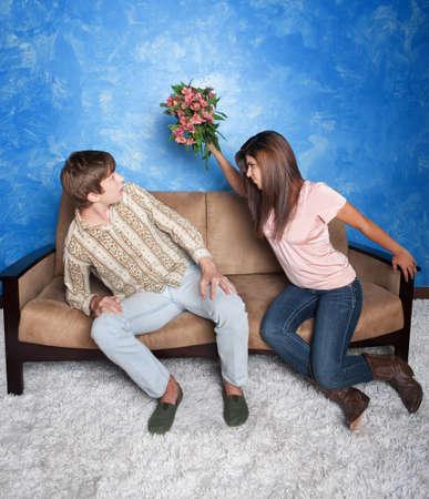 novios enojados: Gestos enojados chica para golpear novio con ramo de flores Foto de archivo
