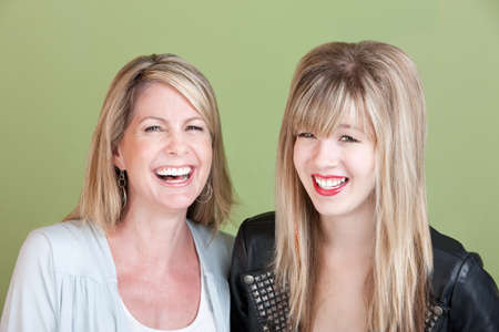 adult 80s: Laughing Caucasian mom and daughter over green background Stock Photo
