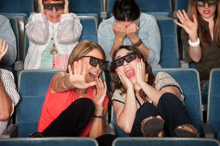 Screaming women with 3D glasses cower in chairs photo