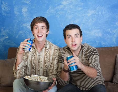Two excited young Caucasian men with soda can and bowl of popcorn 免版税图像