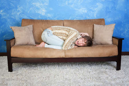 phobia: Scared Caucasian teen in curled up position on sofa