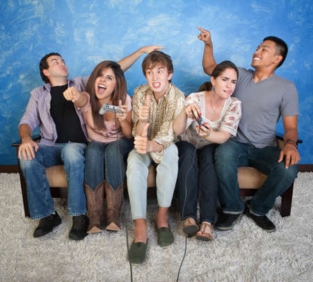 couch: Five excited friends on couch play video game Stock Photo