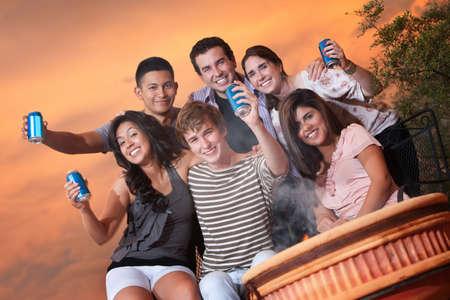 Group of six happy teens in outdoor cookout