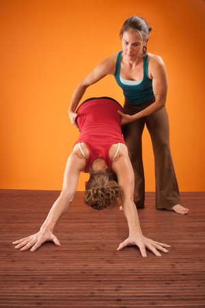 yoga pants: Woman assists her partner in a yogasana workout