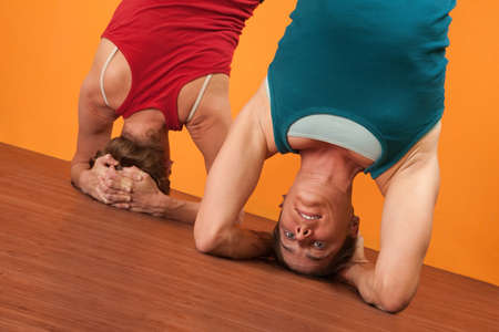 headstand: Two Caucasian women perform Sirasana headstand positions