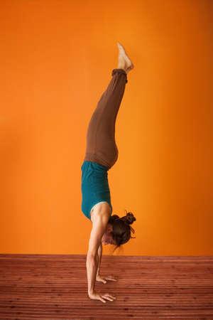 turnanzug: Woman in the Adho Mukha Vriksasana Yoga Position Lizenzfreie Bilder