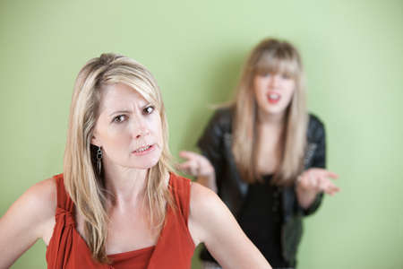 angry blonde: Angry mother with frustrated daughter in the background