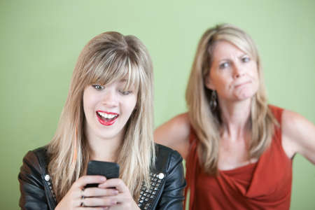 Angry woman behind excited teen on mobile phone photo