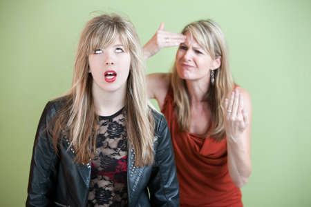 Frustrated mother behind angry daughter in provocative clothing Imagens