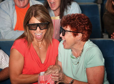 Laughing women in theater with bag of popcorn photo