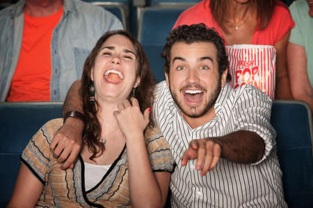 Caucasian couple laugh out loud in theater photo
