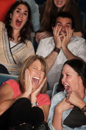 theater audience: Scared group of spectators in theater seats scream in fear