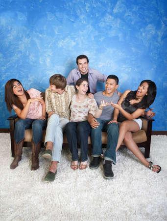 Group of six happy friends on sofa having fun  Stock fotó