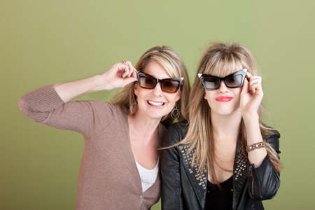 adult 80s: Smiling Caucasian mom and daughter look through sunglasses Stock Photo