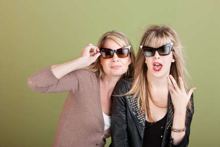 Caucasian mother and daughter with sunglasses over green background photo