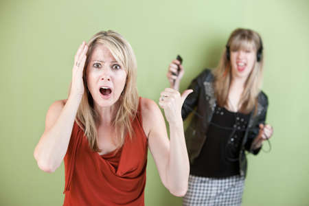 appalled: Annoyed mom with daughter listening on headphones