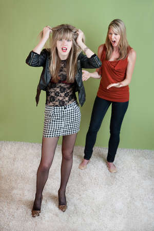 Unhappy mom  with daughter in provocative clothing photo
