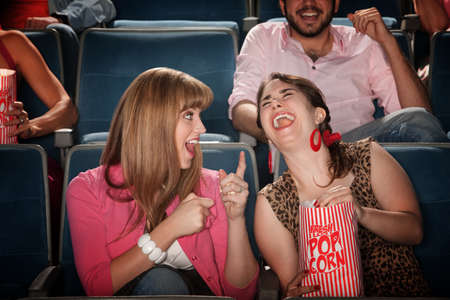 Two pretty young women in the audience laugh together photo