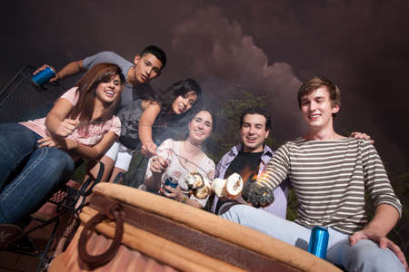 Group of six diverse teenagers roast marshmallows outside photo