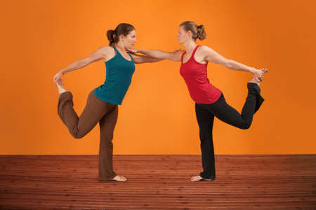 Two Caucasian women perform yogasana over orange background Stock Photo
