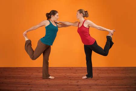 yoga pants: Two Caucasian women perform yogasana over orange background Stock Photo