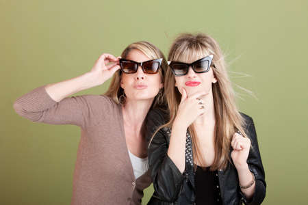 wind blown hair: Mom and daughter with sunglasses over green background gaze