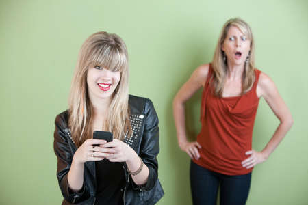 Upset mom with happy teen on mobile phone