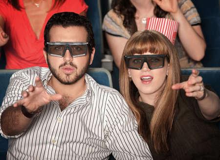 efectos especiales: Sorprendido pareja de raza blanca con gafas 3D en los asientos del teatro