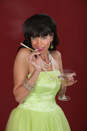 Smiling retro-styled Caucasian woman with martini and cigarette photo