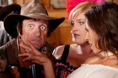 A dusty old cowboy is surprised by the two dangerously beautiful barmaids. photo