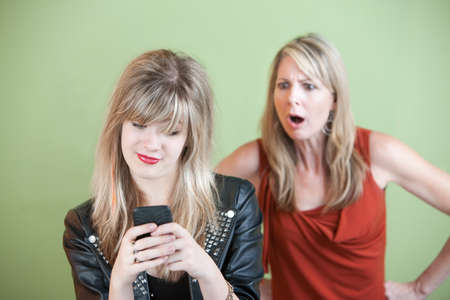 strict: Shocked mom watches teen use phone over green background