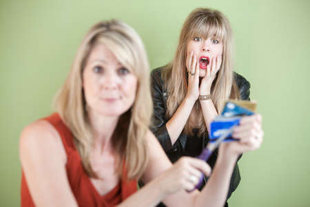 threatens: Mother threatens to cut daughters credit cards with scissors Stock Photo