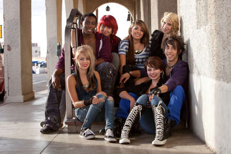 A group of attractive young teen punks sit on a set of stairs while hanging out. photo