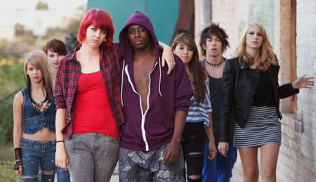 A pair of young punk teens pose together as their friends stay in the background. photo