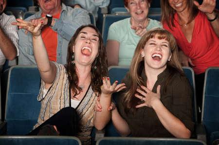 reir: Las mujeres jóvenes reír a carcajadas en el teatro Foto de archivo
