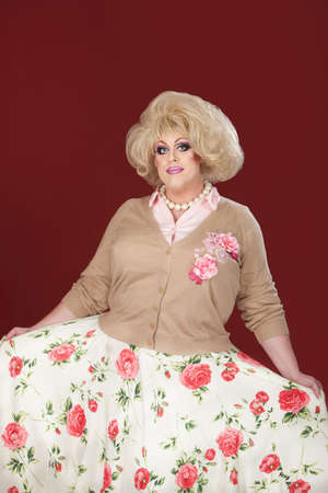 curtsy: Tall, smiling drag queen with floral outfit Stock Photo