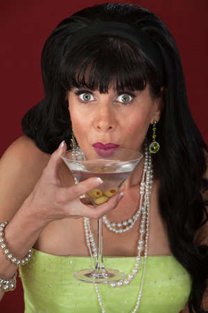 Excited retro-styled Caucasian woman sips martini  photo