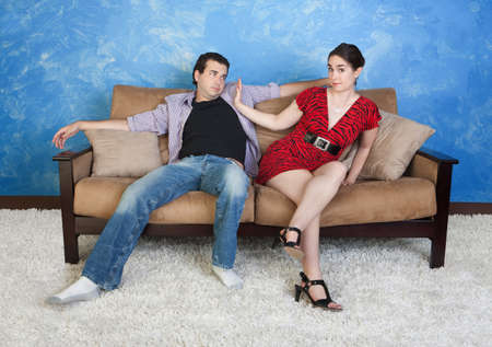 Beautiful woman pushes sloppy man away on sofa photo