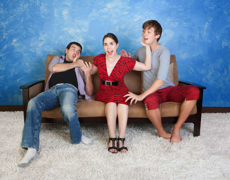 Annoyed young woman slaps two excited men on sofa photo