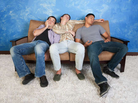 bored man: Three tired young men sleep on a sofa