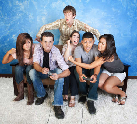 Diverse group of young people fight over video games photo