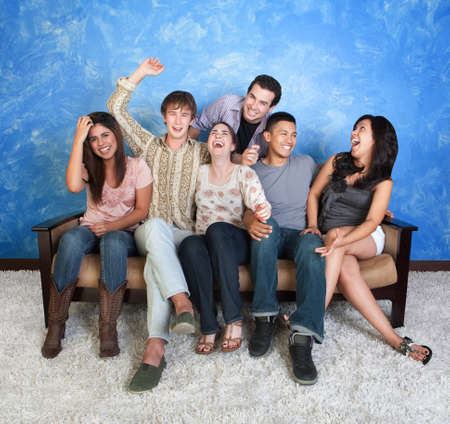 Group of six happy teens on sofa laugh together
