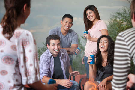 Group of six happy young people socialize outside Stock Photo