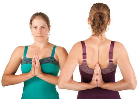 Two women in forward and backward namaskar salutation poses photo