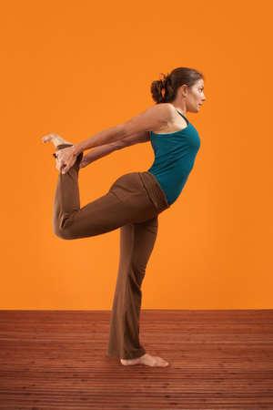 Woman practising yoga stretches her leg backwards