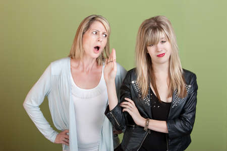 misbehaving: Rude retro-styled daughter gestures angry mom to be silent Stock Photo